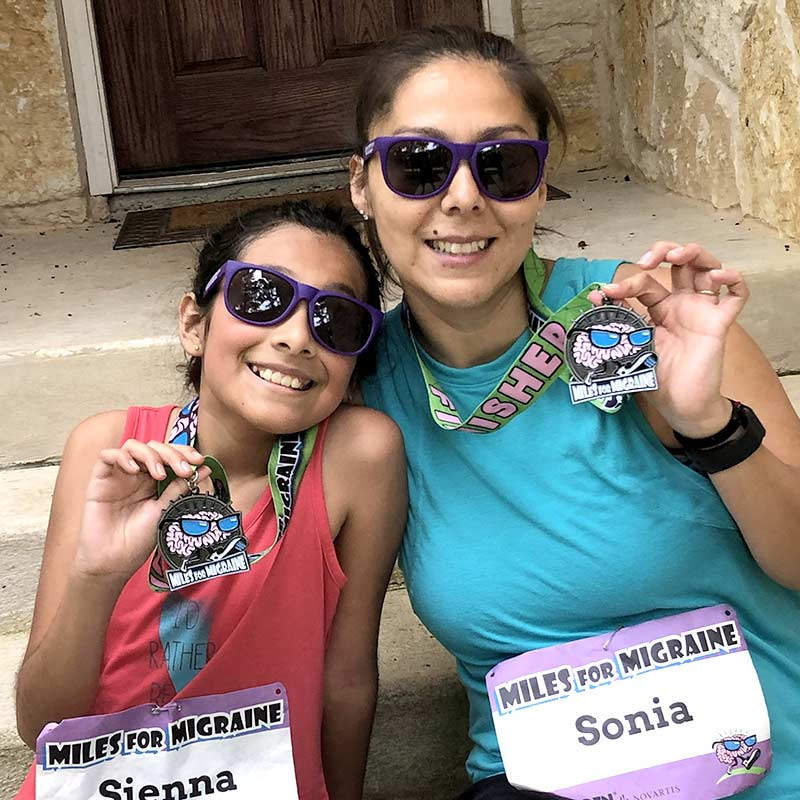 Mother and daughter with sunglasses showing their medals after a race.