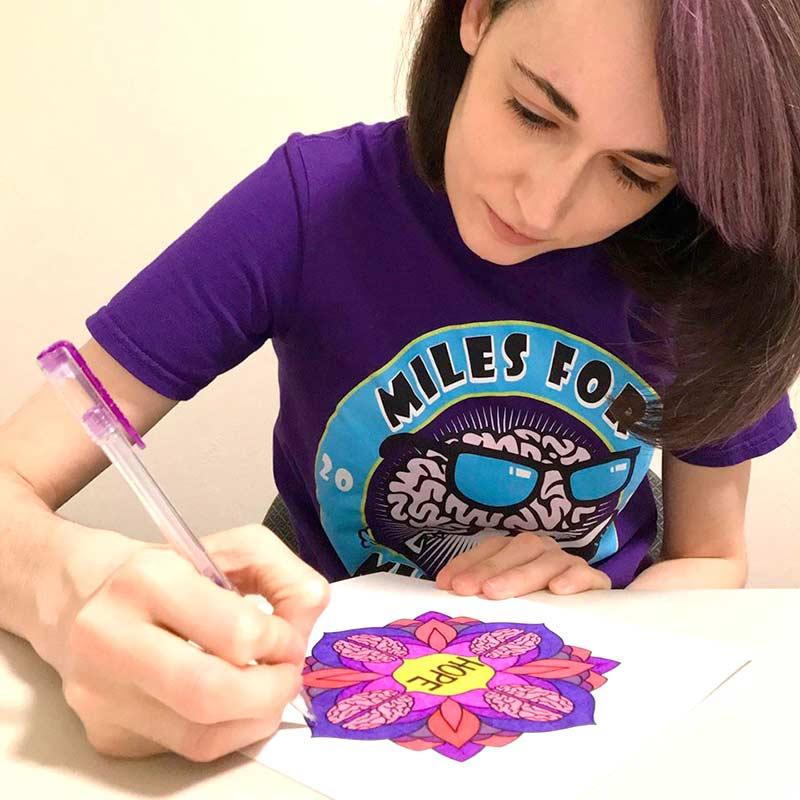a woman drawing a mandala