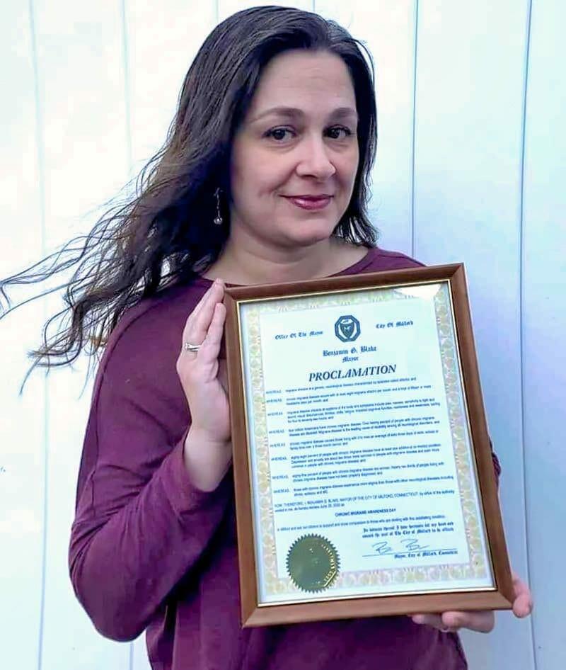 Woman holding a framed proclamaion